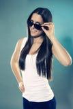 Adolescente bonito que mira sobre sus gafas de sol Fotografía de archivo libre de regalías