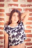 Adolescente bonito que presenta al lado de una pared de ladrillo Foto de archivo