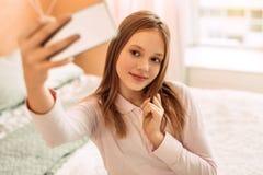 Adolescente bonito que presenta mientras que toma selfies Imágenes de archivo libres de regalías