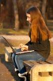 Adolescente bonito que pulsa en el cuaderno en el parque Imagen de archivo