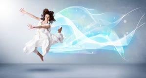 Adolescente bonito que salta com o lenço azul abstrato em torno dela imagem de stock