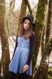 Adolescente bonito que se inclina contra un árbol con un río en el b Foto de archivo libre de regalías