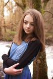Adolescente bonito que se inclina contra un árbol que parece triste Imagen de archivo libre de regalías