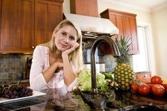 Adolescente bonito que se inclina en contador de cocina Imagen de archivo