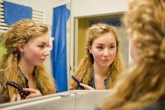 Adolescente bonito que se peina el pelo Imagen de archivo