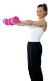 Adolescente bonito que se resuelve con pesas de gimnasia Fotos de archivo