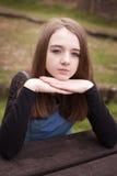 Adolescente bonito que se sienta al aire libre en una mesa de picnic Fotografía de archivo libre de regalías