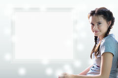 Adolescente bonito que se sienta contra una hoja blanca lugar para su inscripción Imágenes de archivo libres de regalías