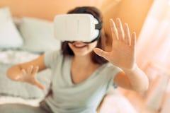 Adolescente bonito que se sienta en cama y las auriculares de prueba de VR Fotos de archivo