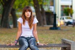 Adolescente bonito que se sienta en el banco Imagenes de archivo