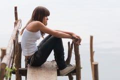 Adolescente bonito que se sienta en el muelle al lado del río en galán Imagen de archivo