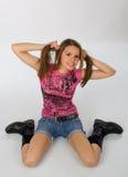 Adolescente bonito que se sienta en el suelo Imagen de archivo