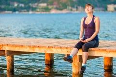Adolescente bonito que se sienta en un embarcadero de madera Imagenes de archivo