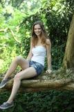 Adolescente bonito que se sienta en una pared del jardín Foto de archivo