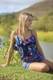 Adolescente bonito que se sienta por un río Fotos de archivo libres de regalías