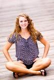 Adolescente bonito que senta 2 equipados com pernas transversais Fotografia de Stock