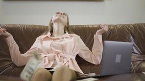 Adolescente bonito que senta-se no sofá de couro na frente do portátil Os dólares que caem na menina, a criança estão sorrindo e filme