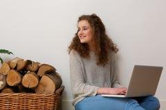 Adolescente bonito que sonríe con el ordenador portátil en casa Foto de archivo