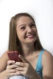 Adolescente bonito que sonríe mientras que en su teléfono móvil Foto de archivo libre de regalías