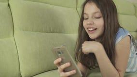 Adolescente bonito que tem o divertimento que comunica-se no vídeo da metragem do estoque do smartphone video estoque