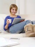Adolescente bonito que usa una tablilla digital Imagen de archivo