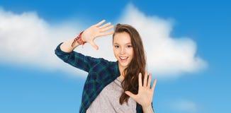 Adolescente bonito sonriente feliz que muestra las manos Imágenes de archivo libres de regalías