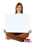 Adolescente bonito sonriente que presenta con el cartel en blanco Imagen de archivo libre de regalías