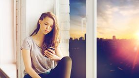 Adolescente bonito triste con mandar un SMS del smartphone Foto de archivo libre de regalías