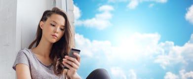 Adolescente bonito triste con mandar un SMS del smartphone Fotografía de archivo libre de regalías