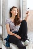 Adolescente bonito triste con mandar un SMS del smartphone Fotos de archivo libres de regalías