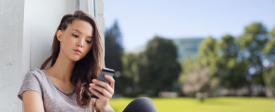 Adolescente bonito triste con mandar un SMS del smartphone Imagenes de archivo