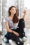 Adolescente bonito triste con mandar un SMS del smartphone Imagen de archivo