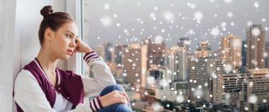 Adolescente bonito triste que mira a través de ventana Fotografía de archivo libre de regalías