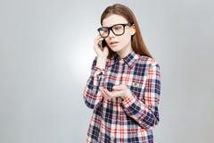 Adolescente bonito triste que se coloca y que habla en el teléfono celular Fotografía de archivo