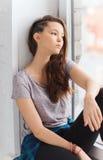 Adolescente bonito triste que se sienta en alféizar Fotos de archivo libres de regalías