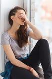 Adolescente bonito triste que se sienta en alféizar Imágenes de archivo libres de regalías