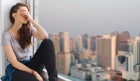 Adolescente bonito triste que se sienta en alféizar Foto de archivo