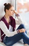 Adolescente bonito triste que se sienta en alféizar Imagen de archivo
