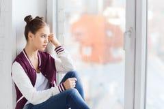Adolescente bonito triste que se sienta en alféizar Foto de archivo libre de regalías