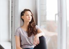 Adolescente bonito triste que se sienta en alféizar Imagen de archivo libre de regalías