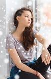 Adolescente bonito triste que se sienta en alféizar Fotografía de archivo libre de regalías