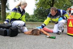 Adolescente borracho en piso con el paramédico Fotografía de archivo libre de regalías