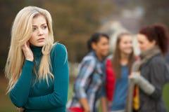 Adolescente bouleversée avec le bavardage d'amis Photographie stock libre de droits