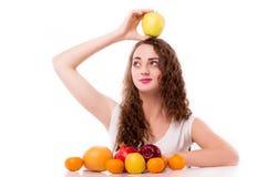 Adolescente brillante con la manzana en la cabeza Fotografía de archivo
