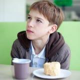Adolescente in caffè che mangia alimenti a rapida preparazione immagini stock