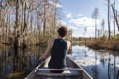 Adolescente canoeing a través de desierto Imagen de archivo libre de regalías