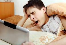 Adolescente cansado con la tableta Foto de archivo libre de regalías