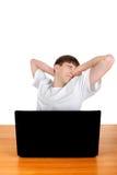 Adolescente cansado detrás del ordenador portátil Imagenes de archivo