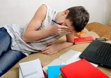 Adolescente cansado que se prepara para el examen Imagenes de archivo