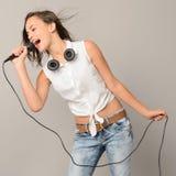 Adolescente cantante con música de karaoke del micrófono Fotos de archivo